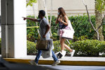 Shoppers walk towards a garage after leaving the Aventura Mall where a shooting left three people injured and several suspects in custody, Saturday, May 8, 2021, in Aventura, Fla. Aventura Police said two groups of people had begun fighting in the mall when shots rang out. (AP Photo/Marta Lavandier)