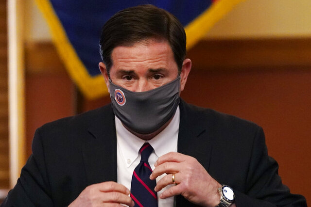 FILE - In this Nov. 30, 2020, file photo, Arizona Gov. Doug Ducey puts his face covering back on after signing election documents to certify the election results for federal, statewide, and legislative offices and statewide ballot measures at the official canvass at the Arizona Capitol in Phoenix. Arizona Republicans voted Saturday, Jan. 23, 2021, to censure Cindy McCain and two prominent GOP officials who have found themselves crosswise with former President Donald Trump. Party activists also reelected controversial Chairwoman Kelli Ward, who has been one of Trump's most unflinching supporters and among the most prolific promoters of his baseless allegations of election fraud. (AP Photo/Ross D. Franklin, Pool, File)