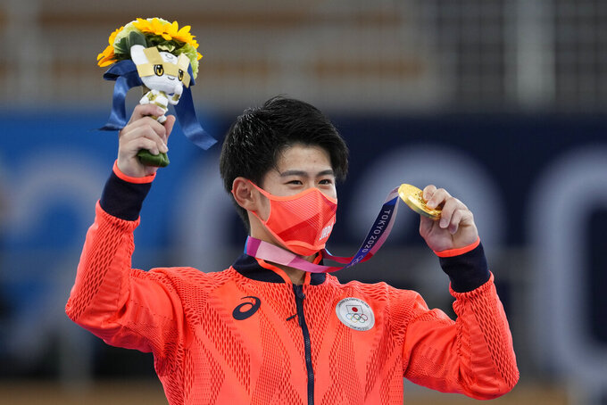 FILE - In this July 28, 2021, file photo, Daiki Hashimoto, of Japan, poses with his gold medal for the artistic gymnastics men's all-around final at the 2020 Summer Olympics in Tokyo. Despite the pandemic, the one-year delay and the soaring costs, the Japanese public may still find a sweet spot for these Olympics, the way it did for the storied 1964 Games. Why? A historic haul of medals. Japan had its best Olympics in every category: the most gold medals (27), the most overall (58), and a third-place finish in both categories behind two much larger countries - the United States and China. (AP Photo/Natacha Pisarenko, File)