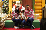 Ariadna and Brian Ferreira wear protective face masks as they pose with their son Enzo with Santa Claus, who is sitting behind a transparent barrier, at Bass Pro Shops, Friday, Nov. 20, 2020, in Miami. This is Santa Claus in the Coronavirus Age, where visits are done with layers of protection or moved online. Putting hundreds of kids a day onto your lap to talk directly into your face — that's not happening. (AP Photo/Lynne Sladky)