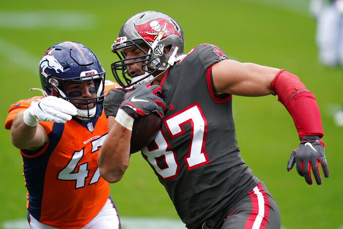 Tampa Bay Buccaneers tight end Rob Gronkowski, right, runs with the ball as Denver Broncos inside linebacker Josey Jewell defends during the first half of an NFL football game Sunday, Sept. 27, 2020, in Denver. (AP Photo/Jack Dempsey)