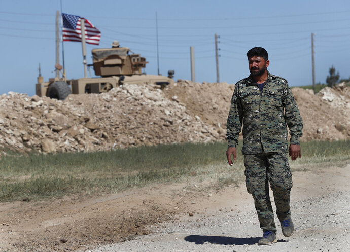 FILE - In this April 4, 2018 file photo, a U.S-backed Syrian Manbij Military Council soldier passes a U.S. position near the tense front line with Turkish-backed fighters, in Manbij, north Syria.  Some hundreds of U.S. troops are stationed in Syria, raising the possibility of an unintended confrontation between two NATO members playing out if Turkey launches an operation in the area.  (AP Photo/Hussein Malla, File)