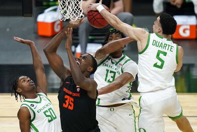 Oregon's Chris Duarte (5) blocks a shot by Oregon State's Dearon Tucker (35) during the first half of an NCAA college basketball game in the semifinal round of the Pac-12 men's tournament Friday, March 12, 2021, in Las Vegas. (AP Photo/John Locher)