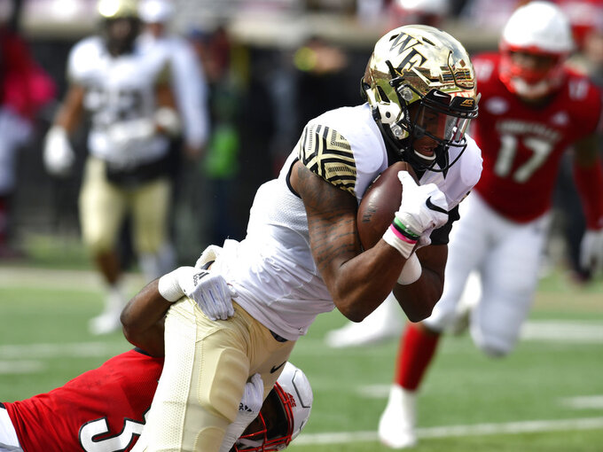 Wake Forest wide receiver Scotty Washington (7) is brought down by Louisville's Cornelius Sturghill (3) during the first half of an NCAA college football game, Saturday, Oct. 27, 2018, in Louisville, Ky. (AP Photo/Timothy D. Easley)