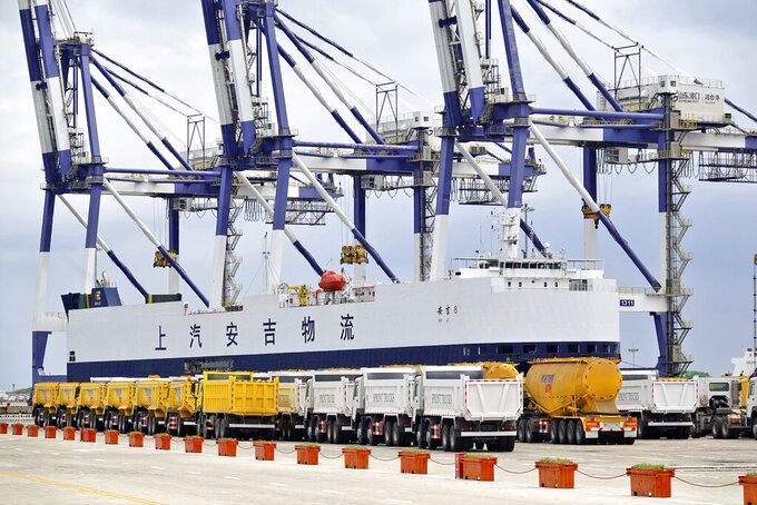Trucks manufactured for export are lined up at a cargo port in Yantai in eastern China's Shandong Province, Friday, July 30, 2021. China's trade rose by double digits in July but growth slowed as global efforts to control the coronavirus's more contagious delta variant weighed on business and consumer spending. (Chinatopix via AP)