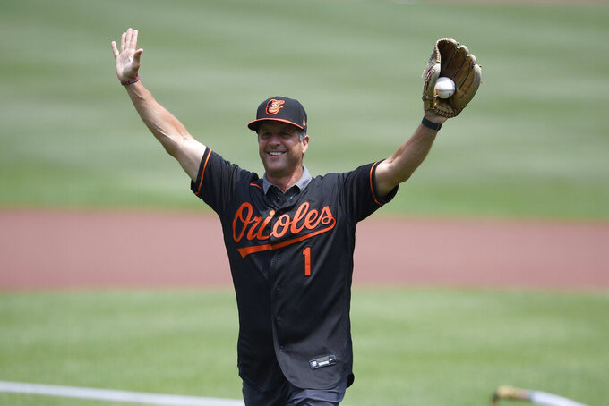Baltimore Ravens head football coach John Harbaugh reacts after he threw out the ceremonial first pitch using a football before a baseball game between the Baltimore Orioles and the Washington Nationals, Sunday, July 25, 2021, in Baltimore. (AP Photo/Nick Wass)