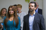 FILE- - In this July 11, 2019, file photo, Donald Trump Jr., the son of President Donald Trump, right, and his girlfriend Kimberly Guilfoyle, listen as President Donald Trump speaks about the 2020 census in the Rose Garden of the White House in Washington. (AP Photo/Alex Brandon, File)