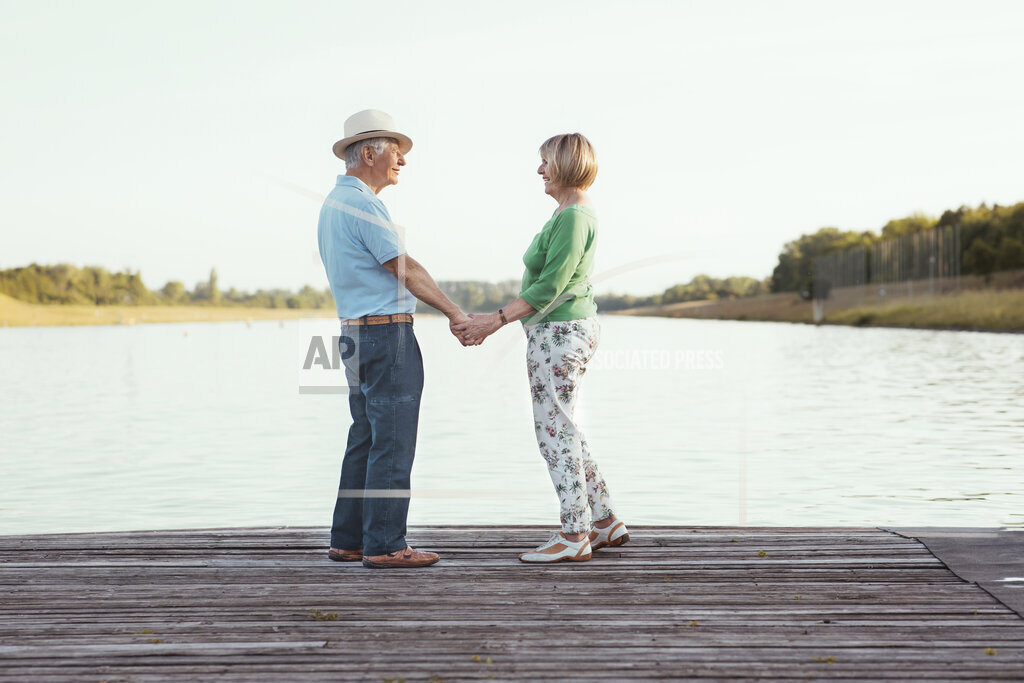 Senior couple holding hands while standing on jetty by lake