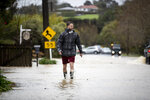 Ryan Jones wades through water in Taupaki near Auckland, New Zealand, on Aug. 31, 2021, after the region was battered with heavy rain making the area's second wettest day since records began in 1943. New Zealand has endured extreme weather events including severe flooding in some places and dry spells in others. (Dean Purcell/New Zealand Herald via AP)
