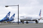 An American Airlines plane taxis past parked Alaska Airlines planes, Thursday, Feb. 13, 2020, at Seattle-Tacoma International Airport in Seattle. American Airlines and Alaska Airlines announced Thursday that they will cooperate more closely on West Coast service, including new American flights from Seattle to India's technology hub in Bangalore. (AP Photo/Ted S. Warren)