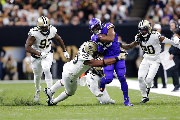 Minnesota Vikings running back Alexander Mattison (25) carries against New Orleans Saints defensive tackle Malcom Brown (90), defensive tackle David Onyemata (93), defensive end Mario Edwards (97) and cornerback Janoris Jenkins (20) in the first half of an NFL wild-card playoff football game, Sunday, Jan. 5, 2020, in New Orleans. (AP Photo/Brett Duke)