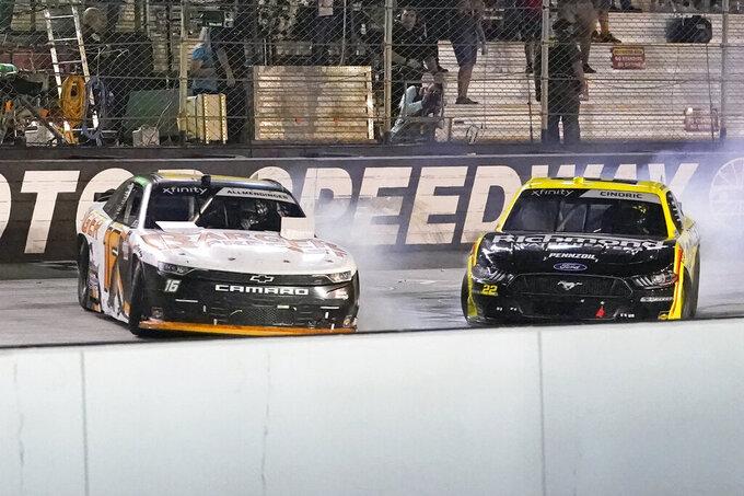 AJ Allmendinger, left, slides across the finish line ahead of Austin Cindric to win a NASCAR Xfinity Series auto race at Bristol Motor Speedway Friday, Sept. 17, 2021, in Bristol, Tenn. (AP Photo/Mark Humphrey)