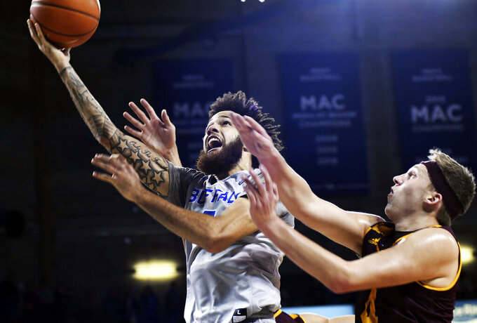 Buffalo's Jeremy Harris, left, goes for a layup past Central Michigan's Mikhail Myles during an NCAA college basketball game in Buffalo, N.Y., Saturday, Feb. 9, 2019. (AP Photo/Heather Ainsworth)