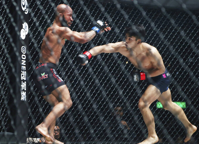 FILE - In this March 31, 2019, file photo, Mixed Martial Arts fighters Demetrious Johnson, left, of the United States and Japan's Yuya Wakamatsu fight during their flyweight One Championship bout in Tokyo. The cage door is locked for the season on the Professional Fighters League, the latest combat sports promotion flattened because of the coronavirus pandemic. (AP Photo/Koji Sasahara, File)