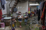 Children of Makkasan preschool walk after receiving meals from their teachers in Bangkok, Thailand Friday, June 19, 2020. During the third month that schools remained closed due to the coronavirus outbreak, teachers have cooked meals, assembled food parcels and distributed them to families in this community sandwiched between an old railway line and a khlong, one of Bangkok's urban canals. (AP Photo/Gemunu Amarasinghe)