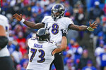 FILE - In this Dec. 8, 2019, file photo, Baltimore Ravens quarterback Lamar Jackson (8) celebrates a 61-yard touchdown play with Marshal Yanda during the second half of an NFL football game against the Buffalo Bills in Orchard Park, N.Y. In their quest to keep quarterback Lamar Jackson upright and running, the Baltimore Ravens have put a priority on fortifying their offensive line following the retirement of eight-time Pro Bowl guard Marshal Yanda. (AP Photo/John Munson, File)
