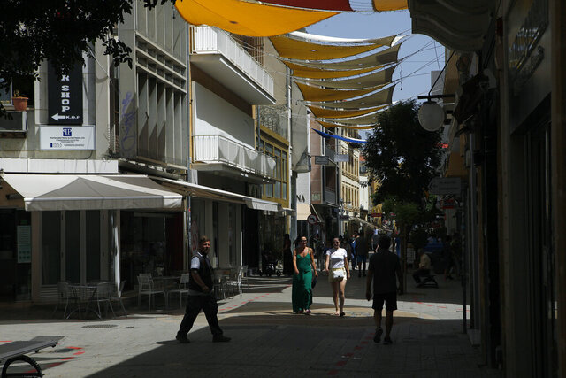 People walk on Ledra street a main shopping street in Nicosia, Cyprus, Thursday, May 21, 2020. Cyprus took a major step toward a return to normality on Thursday when most restrictions of a two month-long stay-at-home order were lifted, allowing primary school kids to return to classes and hair salons and outdoor cafeterias to re-open. (AP Photo/Petros Karadjias)