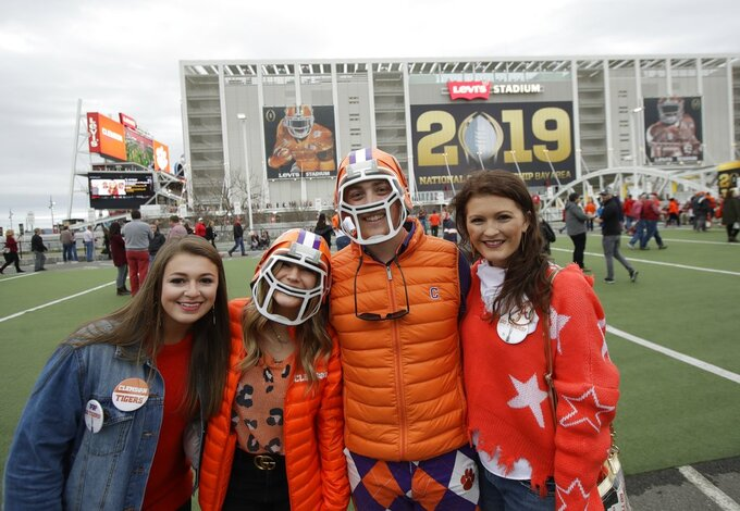 Fans pose outside Levi's Stadium before the NCAA college football playoff championship game between Alabama and Clemson Monday, Jan. 7, 2019, in Santa Clara, Calif. (AP Photo/Jeff Chiu)