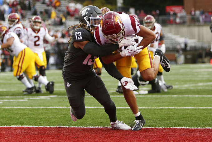 Southern California wide receiver Drake London, right, carries the ball for a touchdown while defended by Washington State linebacker Jahad Woods during the second half of an NCAA college football game, Saturday, Sept. 18, 2021, in Pullman, Wash. Southern California won 45-14. (AP Photo/Young Kwak)
