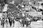 FILE - In this March 17, 1965, file photo, demonstrators walk to the courthouse behind the Rev. Martin Luther King Jr. in Montgomery, Ala. The march was to protest treatment of demonstrators by police during an attempted march. At front and center of march in white shirt is Andrew Young. Today's protests across America against racial injustice are being watched closely by people who five decades ago faced jail cells, bloody assaults, snarling dogs and even potential assassination in the battle against institutional racism. Young, a King lieutenant, marvels at both the sizes and the spontaneity of the protests. The former Democratic congressman, Atlanta mayor and United Nations ambassador recalled activists spending three months to organize for a 1963 Birmingham, Alabama, campaign in which King and other protesters were jailed.    (AP Photo/File)