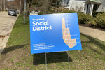 A sign for the social district is seen March 30, 2021, in Saugatuck, Mich. The district is gaining steam as the first establishments get permission from the state to serve to-go alcohol. The district is a creation of the state legislature in response to the COVID-19 pandemic and allows for the consumption of alcohol outdoors in parks and on the streets in Saugatuck's riverfront shopping district, provided the alcohol comes from approved establishments in cups marked with the social district logo. (Carolyn Muyskens/The Holland Sentinel via AP)