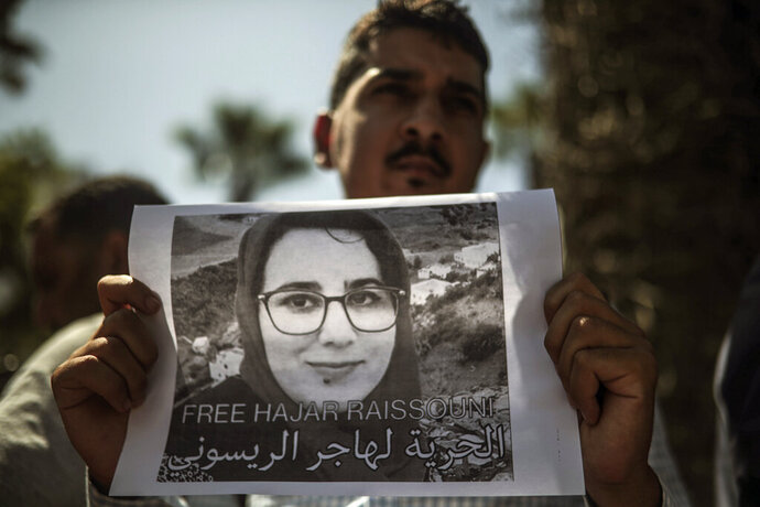 A man carries a banner at a demonstration outside a court in solidarity with detained journalist Hajar Raissouni, in Rabat, Morocco, Monday, Sept. 9, 2019. Banner in Arabic reads