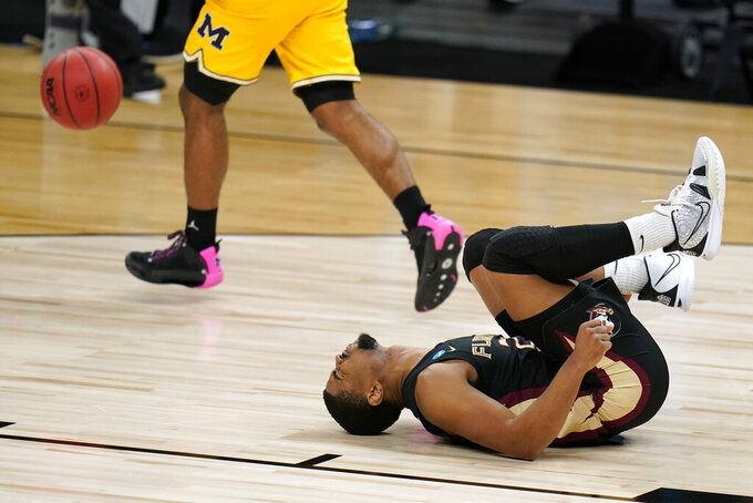 Florida State guard M.J. Walker reacts on the court after getting injured during the second half of a Sweet 16 game against Michigan in the NCAA men's college basketball tournament at Bankers Life Fieldhouse, Sunday, March 28, 2021, in Indianapolis. (AP Photo/Jeff Roberson)