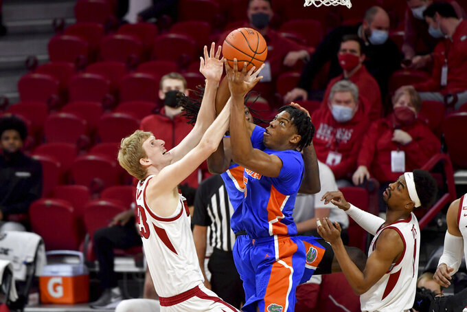 Arkansas forward Connor Vanover (23) and Florida forward Omar Payne (5) fight for a rebound during the first half of an NCAA college basketball game in Fayetteville, Ark. Tuesday, Feb. 16, 2021. (AP Photo/Michael Woods)