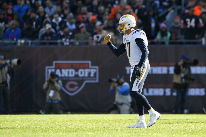 Los Angeles Chargers quarterback Philip Rivers celebrates after throwing an 11-yard touchdown pass to Austin Ekeler during the second half of an NFL football game against the Chicago Bears, Sunday, Oct. 27, 2019, in Chicago. The touchdown pass was Rivers' 400th of his career. (AP Photo/Paul Beaty)