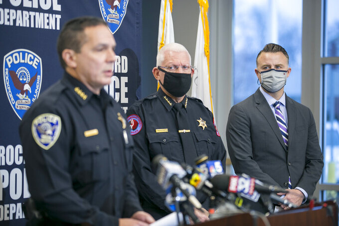 Winnebago County Sheriff Gary Caruana, center, listens as Rockford Police Chief Dan O'Shea, left, identifies the suspected shooter in a triple homicide the night before as Duke Webb, of Florida, during a news conference at Rockford Police Department District 3 on Sunday, Dec. 27, 2020, in Rockford, Ill. Webb, has been charged in the deaths of three people and the wounding of three more in Saturday's shooting at an Illinois bowling alley.  (Scott P. Yates/Rockford Register Star via AP)