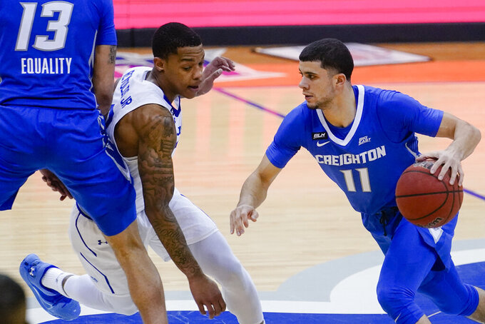Seton Hall's Shavar Reynolds (33) fights through a pick set by Creighton's Christian Bishop (13) as he chases Marcus Zegarowski (11) during the first half of an NCAA college basketball game Wednesday, Jan. 27, 2021, in Newark, N.J. (AP Photo/Frank Franklin II)