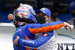 Scott Dixon, of New Zealand, is congratulated by Alex Palou, of Spain, after Dixon won the pole for the Indianapolis 500 auto race at Indianapolis Motor Speedway, Sunday, May 23, 2021, in Indianapolis. (AP Photo/Darron Cummings)