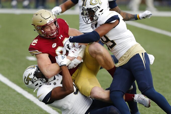 Georgia Tech defensive backs Tre Swilling, bottom, and Wesley Walker, right, tackle Boston College tight end Hunter Long during the first half of an NCAA college football game Saturday, Oct. 24, 2020, in Boston. (AP Photo/Michael Dwyer)