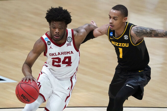 Oklahoma guard Elijah Harkless (24) drives past Missouri guard Xavier Pinson (1) during the first half of a first-round game in the NCAA men's college basketball tournament at Lucas Oil Stadium, Saturday, March 20, 2021, in Indianapolis. (AP Photo/Darron Cummings)