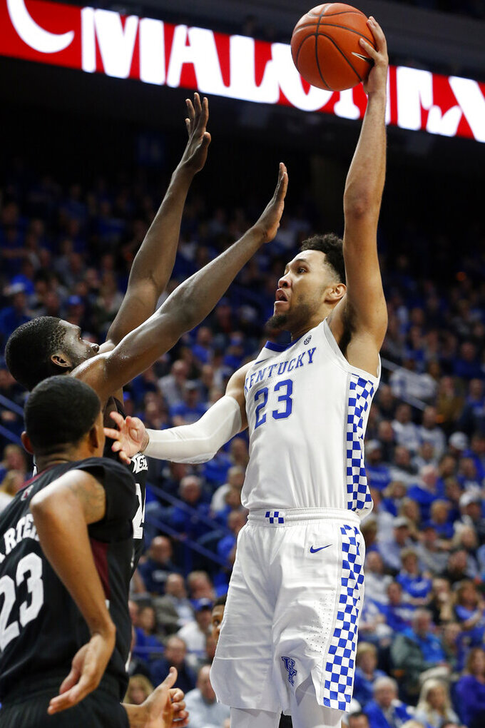 Kentucky's EJ Montgomery (23) shoots while defended by Mississippi State's Tyson Carter, left, and Abdul Ado during the second half of an NCAA college basketball game in Lexington, Ky., Tuesday, Feb. 4, 2020. Kentucky won 80-72. (AP Photo/James Crisp)