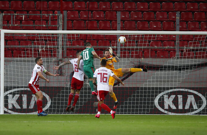 Olympiakos' goalkeeper Jose Sa, right, makes a save in front of Wolverhampton Wanderers' Daniel Podence, center, during the Europa League round of 16 first leg soccer match between Olympiakos and Wolverhampton Wanderers at the Karaiskakis Stadium in Piraeus, Greece, Thursday, March 12, 2020. The match is being played in an empty stadium because of the coronavirus outbreak. (AP Photo/Thanassis Stavrakis)