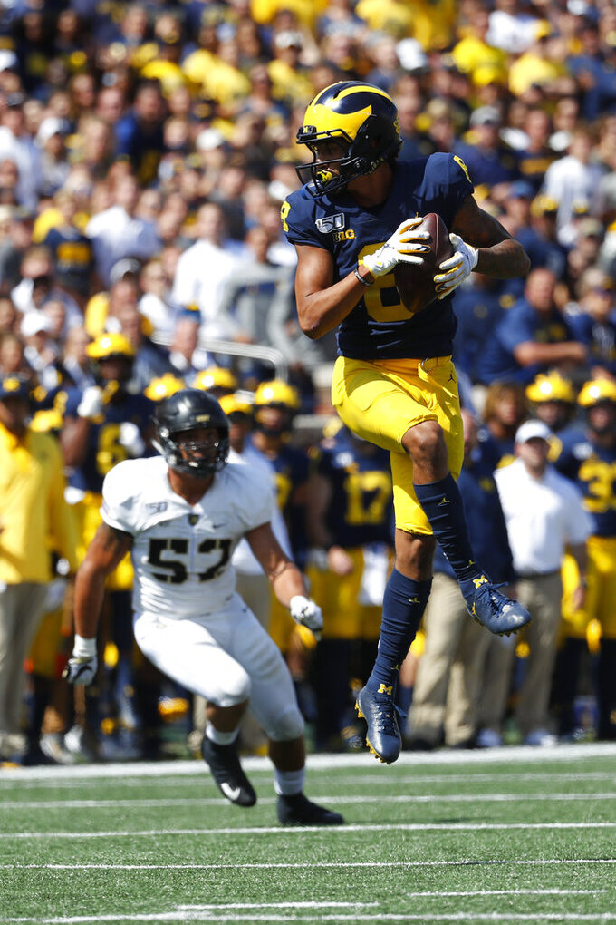 Michigan wide receiver Ronnie Bell (8) catches a pass as Army linebacker Amadeo West (52) defends in the second half of an NCAA college football game in Ann Arbor, Mich., Saturday, Sept. 7, 2019. Michigan won 24-21 in overtime. (AP Photo/Paul Sancya)
