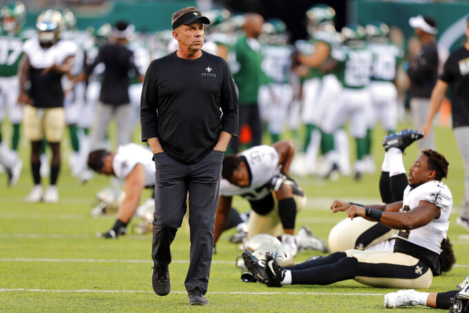 FILE - In this Aug. 24, 2019, file photo, New Orleans Saints coach Sean Payton looks at his team as players warm up for a preseason NFL football game against the New York Jets in East Rutherford, N.J. It's the offseason for the NFL, but the need for social distancing and self-isolation by the pro football community was driven home Thursday when New Orleans coach Sean Payton announced he was the first in the NFL to test positive for COVID-19.(AP Photo/Noah K. Murray, File)