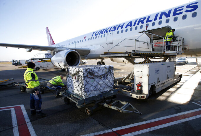 Workers unload boxes of the Astra Zeneca vaccine at the Belgrade Airport, Serbia, Sunday, Feb. 21, 2021. 150,000 doses of Astra Zeneca vaccines were delivered to Serbia. (AP Photo/Darko Vojinovic)