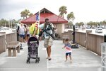 """Michael Taylor, also known as """"The Armed Fisherman"""" walks along Pier 60 in in Clearwater Beach, Fla., with his 2-year-old daughter Ocean and his assault rifle and fishing gear, on Saturday, July 3, 2021. (Octavio Jones/Tampa Bay Times via AP)"""