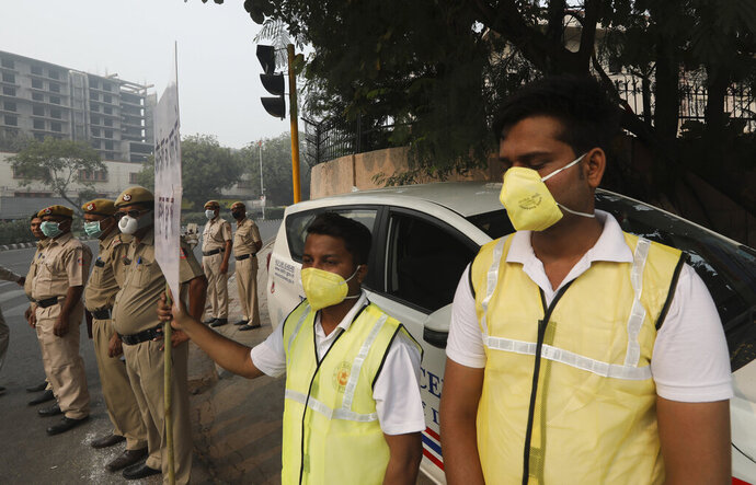 Volunteers and policemen wear pollution masks and stand at a busy crossing with the banner saying obey odd and even, remove pollution, in New Delhi, India, Monday, Nov. 4, 2019. Authorities in New Delhi are restricting the use of private vehicles on the roads under an