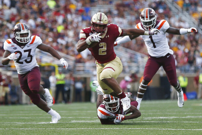 FILE - In this Aug. 31, 2019, file photo, Boston College running back AJ Dillon (2) breaks a tackle on Virginia Tech defensive back Jermaine Waller, bottom, on a touchdown run during the first half of an NCAA college football game, in Boston. Dillon was selected to The Associated Press All-Atlantic Coast Conference football team, Tuesday, Dec. 10, 2019. (AP Photo/Michael Dwyer, File)