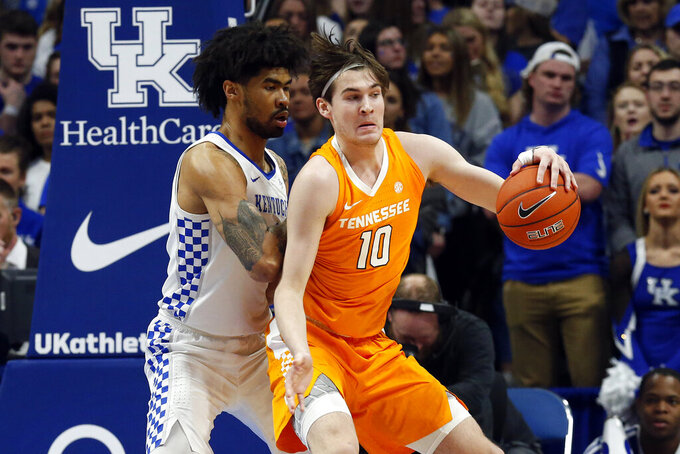 Tennessee's John Fulkerson (10) looks for an opening on Kentucky's Nick Richards, left, during the first half of an NCAA college basketball game, Tuesday, March 3, 2020, in Lexington, Ky. (AP Photo/James Crisp)