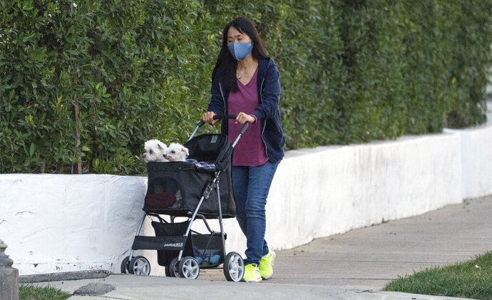 A woman wears a mask as she takes two small dogs in a stroller for a walk in Los Angeles Thursday, Jan. 7, 2021. California health authorities reported Thursday a record two-day total of 1,042 virus deaths, with many people infected during the surge after Halloween and Thanksgiving. The California Hospital Association says the state is moving too slowly to find ways to handle so many cases. (AP Photo/Damian Dovarganes)
