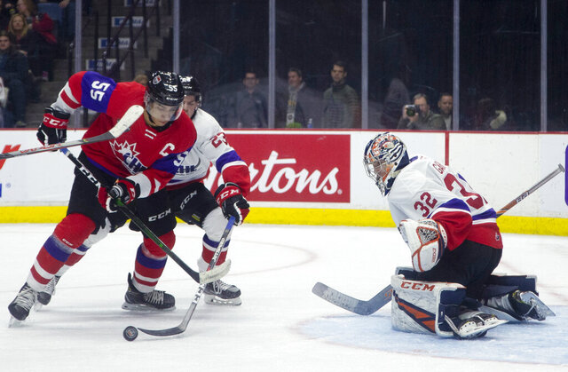 FILE - In this Thursday, Jan. 16, 2020, file photo, Team Red center Quinton Byfield (55) moves in on Team White goaltender Dylan Garand (32) while defended by Jack Thompson (23) during the second period of hockey's CHL Top Prospects Game in Hamilton, Ontario. Byfield is one of the top NHL draft prospects. (Peter Power/The Canadian Press via AP, File)