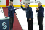 Seattle Kraken head coach Dave Hakstol, left, is welcomed by team CEO Tod Leiweke, center, and general manager Ron Francis, Thursday, Sept. 9, 2021, during a media event for the grand opening of the Kraken's NHL hockey practice and community facility in Seattle. (AP Photo/Ted S. Warren)