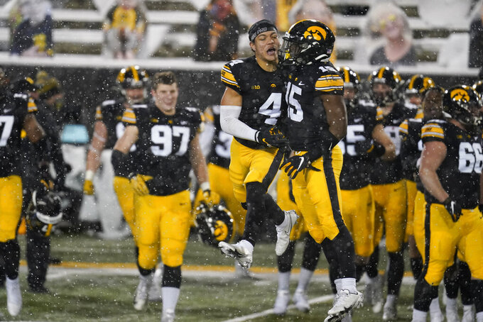 Iowa defensive back Dane Belton (4) celebrates with teammate Tyler Goodson (15) at the end of an NCAA college football game against Wisconsin, Saturday, Dec. 12, 2020, in Iowa City, Iowa. Iowa won 28-7. (AP Photo/Charlie Neibergall)