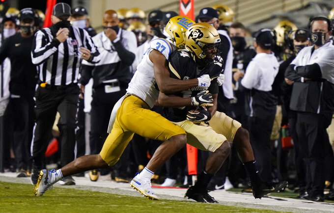 UCLA defensive back Quentin Lake, left, stops Colorado wide receiver Dimitri Stanley after he caught a pass in the first half of an NCAA college football game Saturday, Nov. 7, 2020, in Boulder, Colo. (AP Photo/David Zalubowski)