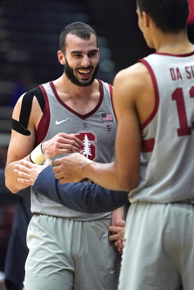 Stanford center Josh Sharma (20) celebrates with teammates as he walks back to the bench during the second half of the team's NCAA college basketball game against UCLA, Saturday, Feb. 16, 2019, in Stanford, Calif. Stanford won 104-80. (AP Photo/Tony Avelar)