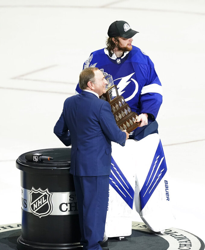 National Hockey League Commissioner Gary Bettman hands the Conn Smythe award to goaltender Andrei Vasilevskiy after the NHL hockey Stanley Cup finals against the Montreal Canadiens, Wednesday, July 7, 2021, in Tampa, Fla. The award is given to the most valuable player to his team in the playoffs. Vasilevskiy was selected the winner in a vote by a panel of the Professional Hockey Writers Association. (AP Photo/Gerry Broome)